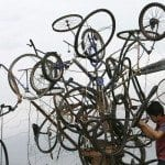 A fine arts student gives last-minute touches to a bicycle tree he built out of junk materials in front of the Cultural Center in Manila in preparation for Earth Day Celebrations.. REUTERS/Romeo Ranoco