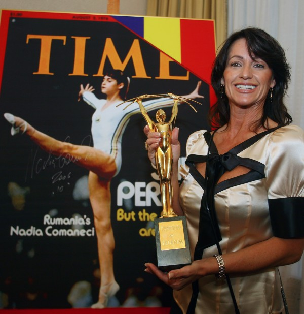 "Romanian Olympic gold medal gymnast Comaneci holds the ""Legendary Champions"" trophy in Bucharest. REUTERS/Bogdan Cristel"