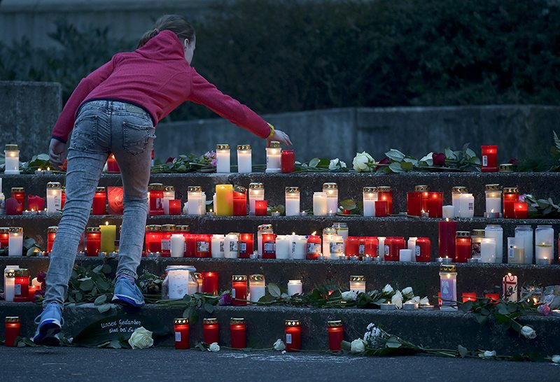 A student places a lit candle outside the Josef-Koenig-Gymnasium high school in Haltern am.