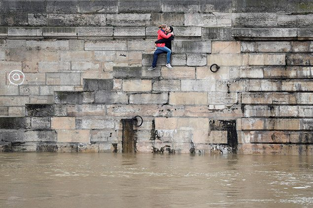 A couple exchanges kisses on the bank as high waters causes flooding along the Seine River in Paris. REUTERS/Charles Platiau