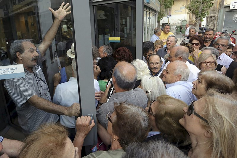 Pensioners struggling to enter a National Bank branch to receive part of their pension in Iraklio, Crete. REUTERS/Stefanos Rapanis
